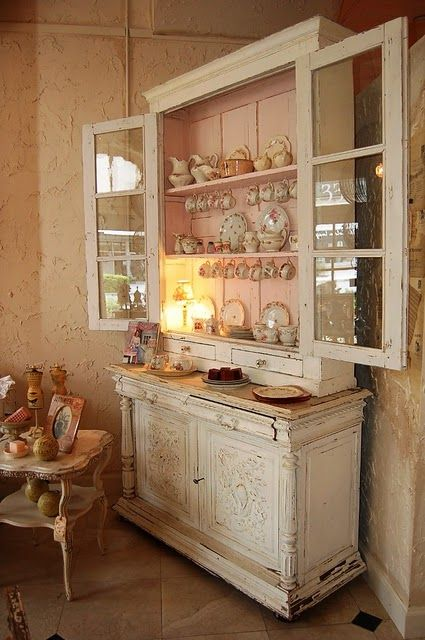 Love this distressed cabinet w/ the pink back board.
