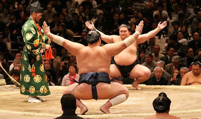 Sports: This is a photo of two sumo wrestlers. Sumo wrestlers do this before matches. Sumo wrestling is a very popular sport in Japan. The object of the game is to throw your opponent out of the circle they are standing in. Another popular sport in Japan is baseball. the Japan league is the NPB (Nippon Professional Baseball). Its a competitive league and fans love watching their games. Some other sports include karate, martial arts, football, surfing, and figure skating.