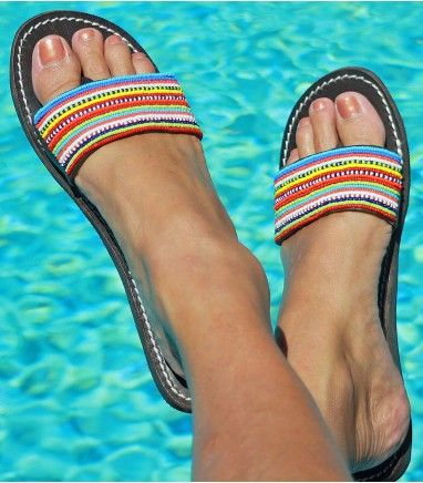 This fun beaded leather sandal has bright rows of stripes across a thick leather strap, with a hidden toe post for extra comfort.         This product is handmade in Africa    Thong Style Sandal    Genuine Dark Leather Upper (dyed & sun dried) with contrast white stitching    Flat Flexible (non slip) Rubber Sole    Hand-cut uppers and soles    All bead work sewn by hand