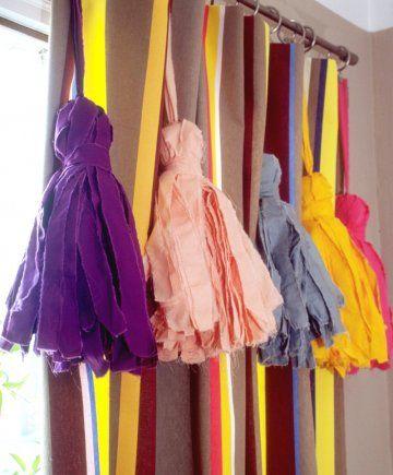 des pompons géant comme de la passementerie réalisés en chiffon de couleur accrochés à une tringle à rideaux