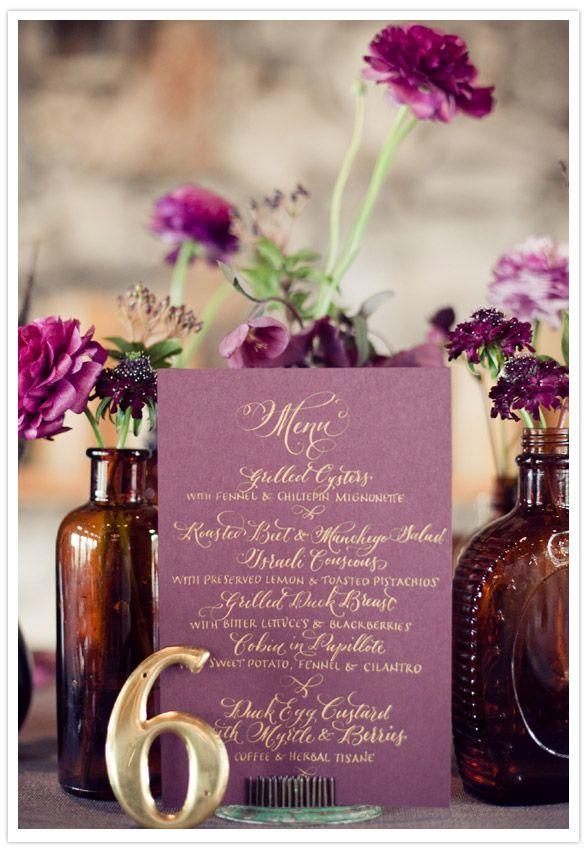 Pretty purple menu cards nestled between vintage bottles with purple blooms