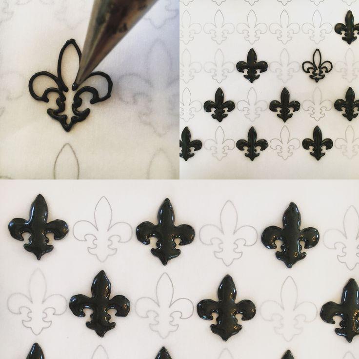 Fleur de lis royal icing transfers - tutorial  http://www.sugarhighnola.com/fleur-de-lis-royal-icing-transfers/