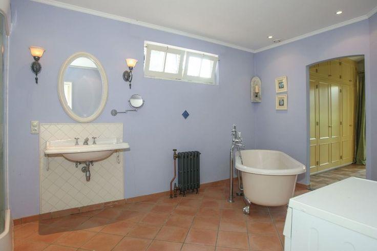 Woonstijl terug naar de kust met  grote witte ovale spiegel op zomerlucht blauwe muren in de badkamer