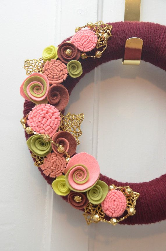 Cranberry Cocktail  This 12 yarn cover wreath is covered in cranberry yarn. It has 15 handmade felt flowers. Flower colours are strawberry, chartreuse, pea green, rust brown and pink sandalwood. It is accented with gold glitter ball garland and gold glitter leaves.*  A beautiful cranberry Christmas wreath.  *(*Please Note: Not all wreaths are exactly as shown due to each one being created individually. If this wreath is ordered it will, however, follow the colour scheme as shown. Gold…