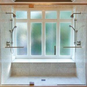 Diese Übergangszeit Badezimmer hat Mini Marmorfliesen, eine Bank und zwei Duschköpfe in einem geschlossenen Raum. / Foto: Addhouse