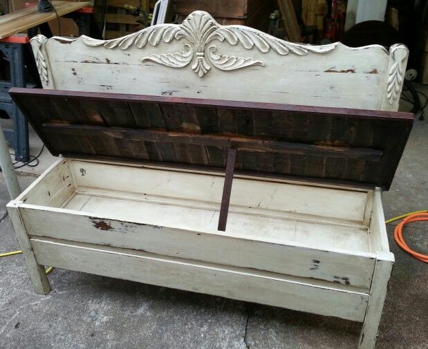 Bench made from headboard and pallets with the seat open to reveal storage.