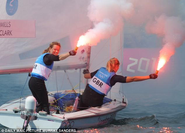 Saskia Clark and Hannah Mills light flares in celebration of their win - silver medal in 470 class sailing