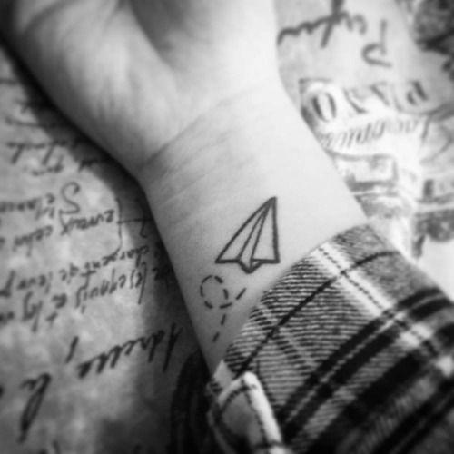 Paper plane tattoo on the left inner wrist.