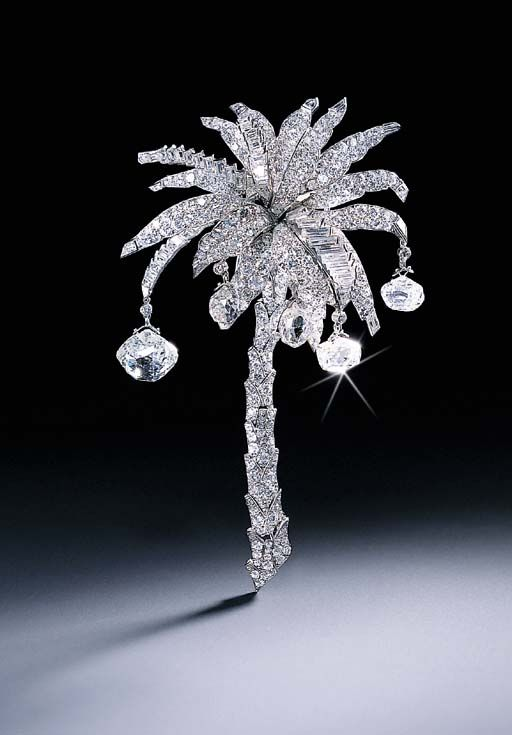 THE CARTIER PALM TREE DIAMOND CLIP BROOCH   Set with circular and baguette-cut diamond leaves with briolette-cut diamond coconuts to the pavé-set articulated trunk, 1939,