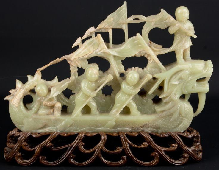 Description A Chinese hardstone 'Jade' model of a river dragon-boat. The vessel shown with enthusiastic rowers on each side while the boat is helmed at the stern. The bow with dragon head while the boat flies a number of pennants with a boy standing on the head of the dragon with a partly unfurled flag. The stone of pale green tones.  Date 19th century. Qing Dynasty  www.collectorstrade.de