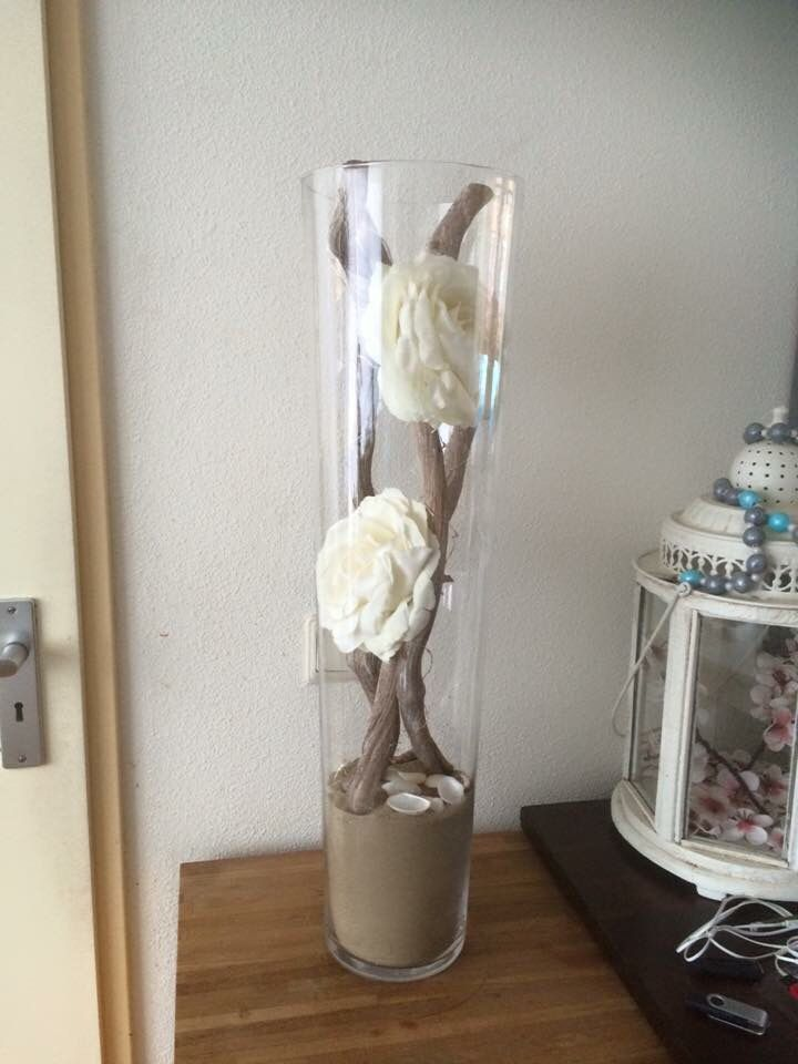 Gave vaas met rozen, takken en zand.
