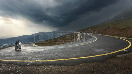 transalpina: Riding a motorcycle toward the storm at the highest and most dangerous asphalt road in Romania. Transalpina highway.