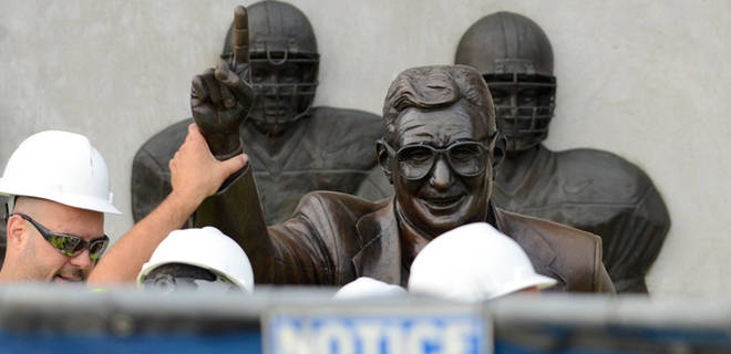 Workers handle the statue removal of former Penn State football coach Joe Paterno.