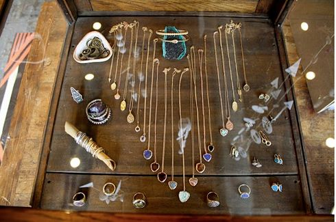 Love this layered jewelry display! Especially the semi-precious stones used to display bracelets and what looks like a stick used to display rings!