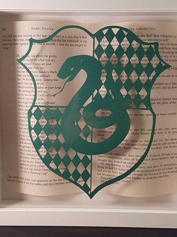 A perfect present for the proud Slytherin in your life. This is a handmade framed art work is made with pages from the book behind a papercutting. The snake house crest design is hand cut in green paper and rests on the glass in front. Pages from the Harry Potter book are in the background on the shadow box frame. Framed in white. The frame is square 25 cm x 25 cm. Something special for yourself or a brilliant and unique gift for someone who is a fan! TERMS AND CONDITIONS PLEASE NOTE: *...