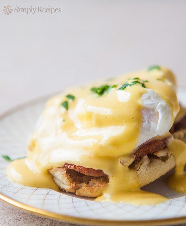 Eggs Benedict! Poached eggs over bacon and buttered toasted English muffin, topped with Hollandaise sauce. #MothersDay On SimplyRecipes.com