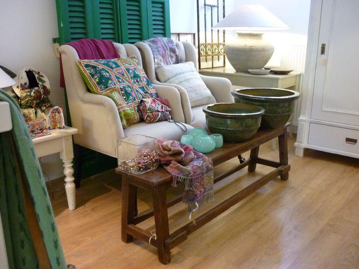 Interieur in groen en roze; gecapitonneerde stoelen, oud bankje uit India, groen louvreluiken.