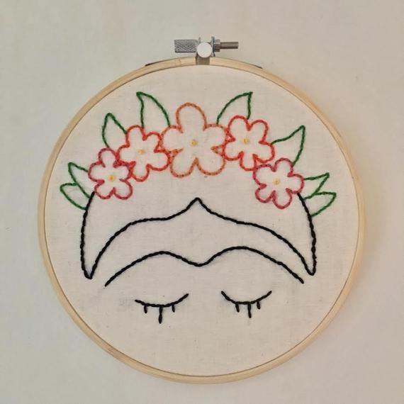 This hand stitched embroidery hoop features a minimalist design of Frida Kahlo with a flower crown. DETAILS: 6 inch wood embroidery hoop Lightweight and finished with cotton fabric on the back Made to Order, Variation May Occur Flower Embroidery Designs, Hand Embroidery Stitches, Embroidery Hoop Art, Cross Stitch Embroidery, Mexican Embroidery, Couture, Flower Crown, Minimalist Design, Cotton Fabric