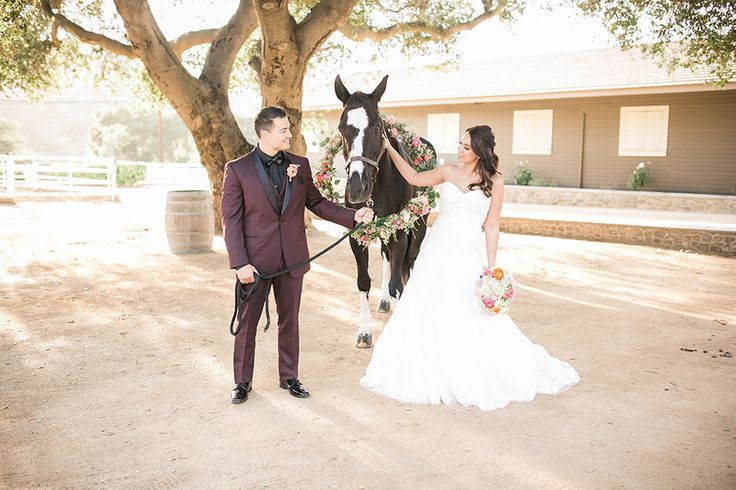 Giracci farms outdoor rustic wedding bride a line strapless gown with a sweetheart neckline and lace detail with groom burgundy shawl lapel tuxedo with black dress shirt and black faux leather bow tie with floral boutonniere standing by horse