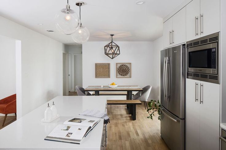 Kitchen and Dining overall view - St. Johns Remodel and Addition.  #jamesoninteriors #mywestelm #midcentury #modern #gray #whiteoak #Austin #globe #pendants #polyhedron #chandelier