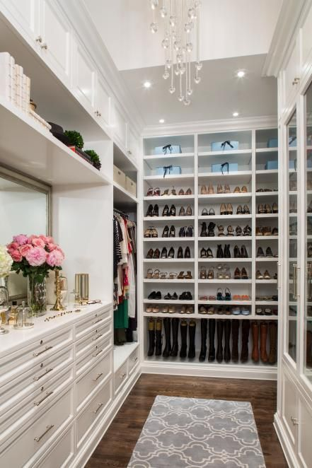 Cabinetry and shelving extend to the ceiling to maximize storage, and customized compartments hold everything from jewelry to boots to hats to dresses, keeping the transitional space organized and efficient.