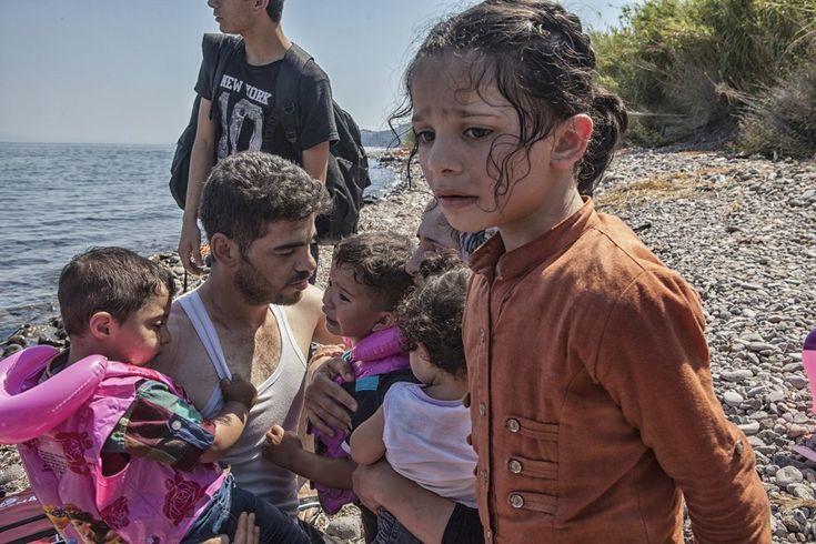 Un hombre consuela a sus hijos momentos después de desembarcar en la costa norte de la isla Lesbos tras cruzar el Mar Egeo en un una barca de plástico. Según Unicef, uno de cada 200 niños en el mundo ha tenido que huir de su hogar por la guerra y otros conflictos.