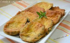 Ecco le frittelle di melanzane alla curcuma. Si tratta di melanzane tagliate a fette che vengono panate al sapore di curcuma e fritte.