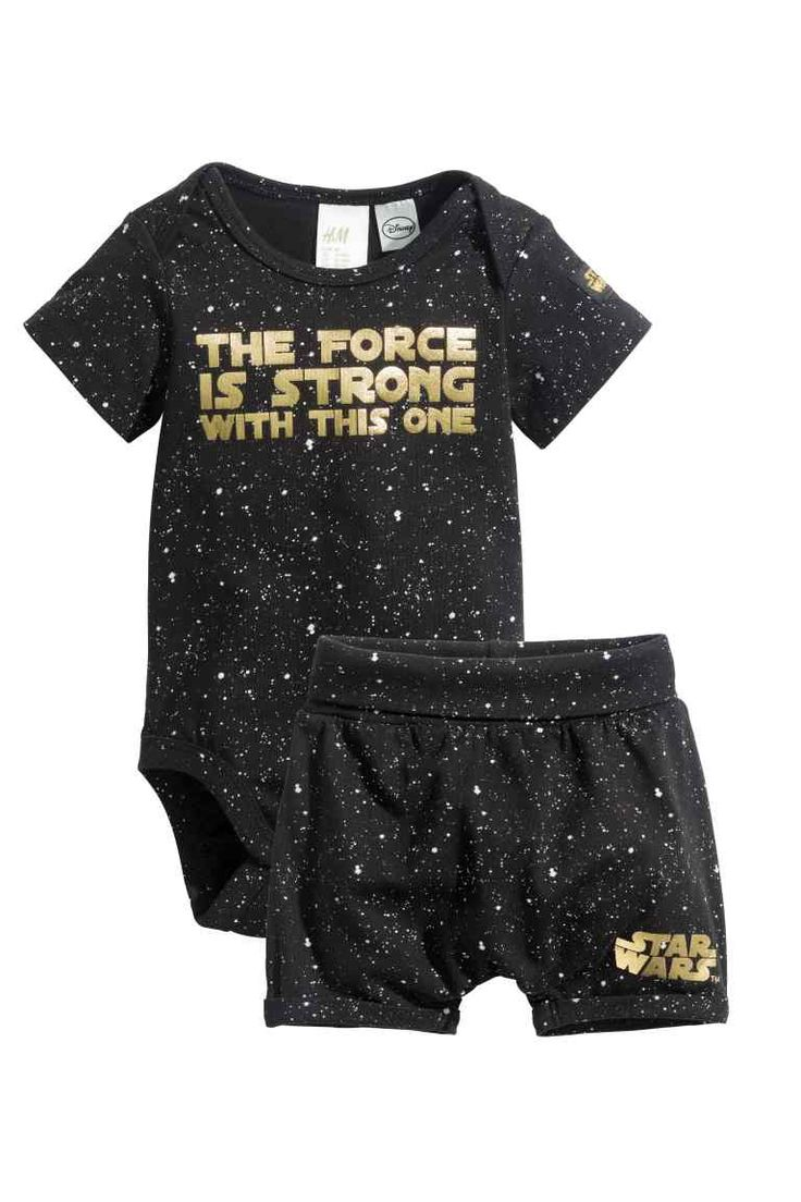 Bodysuit and shorts: Set in soft, patterned cotton jersey. Short-sleeved bodysuit with a gold-coloured text print on the front, lap shoulders and press-studs at the crotch. Shorts with wide foldover ribbing at the waist, sewn-in turn-ups at the hems and a gold-coloured text print on one leg.