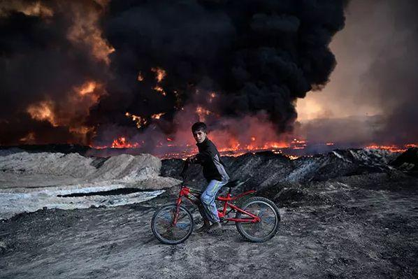 Αγόρι σταματά μπροστά σε κοίτασμα πετρελαίου που πυρπολήθηκε από μαχητές του Ισλαμικού Κράτους πριν από την επίθεση της Μοσούλης στο Ιράκ.