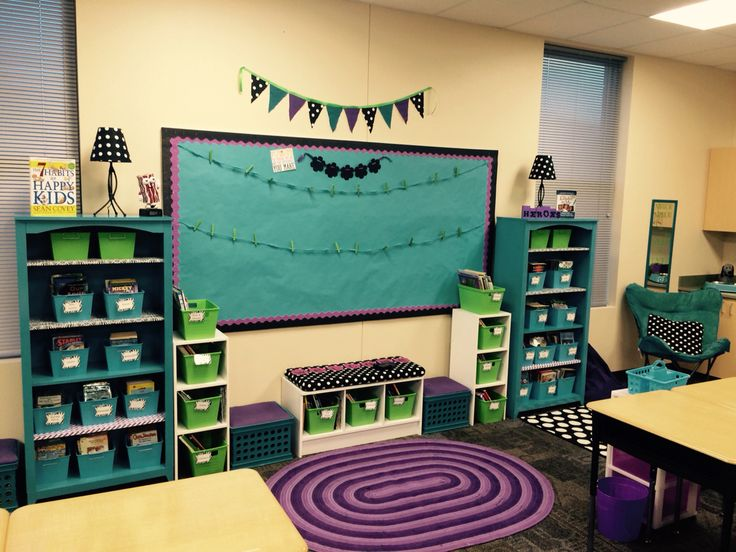 Classroom library, pride bulletin board, purple rug, polka dot lamps