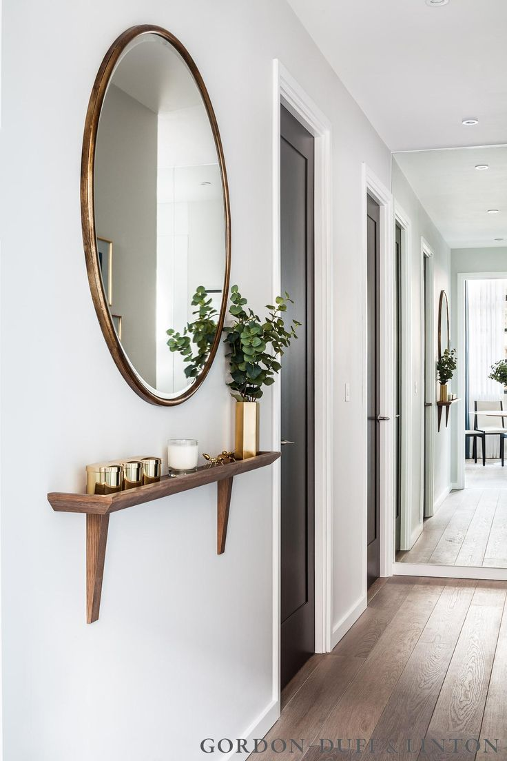 Don't think a narrow hallway is destined to be bare. A narrow shelf and large mirror are a great way to play up this empty space.