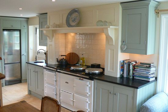An English Cottage Kitchen. I love the pristine white Aga Cooker with display mantle above it and the blue gray shaker cabinets.