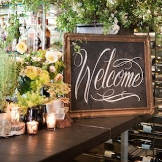 Photo courtesy of Grey Likes Weddings. Love the candles, florals, and chalkboard welcome sign.