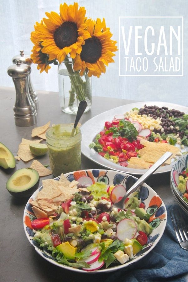 Vegan Taco Salad with corn, black beans, red bell pepper, tomatoes, radish, avocado, tortilla chips and avocado dressing