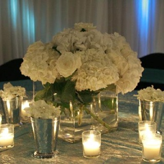 classic, romantic centerpieces....I wouldn't want plain white.  I'd want some blue and coral as the main flower color with white accents.