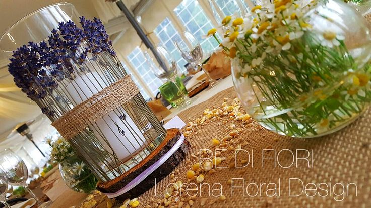 Centrotavola countrychic. Tronco e vaso di vetro decorato a mano con lavanda e juta, contornati da due boule con fiori e grano+mais sul tavolo.