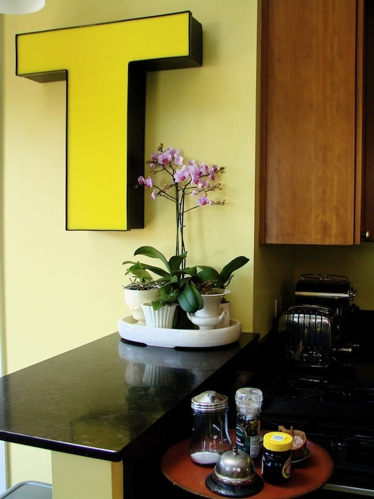 """It's Random, it's Yellow, it's Bold and it's Big - the """"T"""" Alphabet letter wall mounted. Look like it should light up? I just love it. Love it. Love the collection with the plants as well, grouped on a tray make them so tidy. Delicious!"""