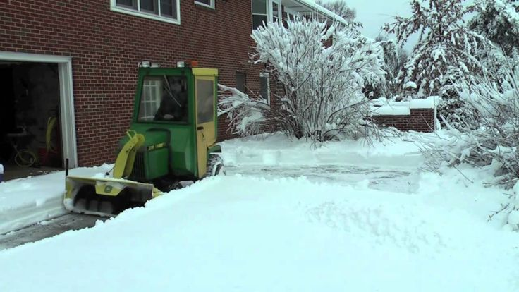 John Deere 318 throwing snow. Looks like it needs more power to me. Onan 2 cyl engine 43 CI.