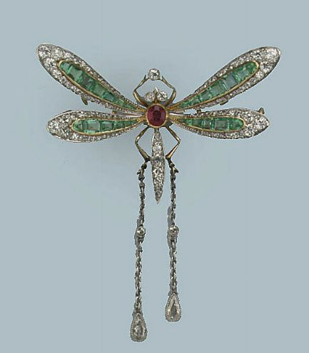 A GEM SET AND DIAMOND BUTTERFLY BROOCH   The wings set with lines of graduated emeralds flanked by cushion-shaped and rose-cut diamonds to the ruby and diamond set abdomen, supporting two chains terminating in pear-shaped diamond set drops, French marks, circa 1930