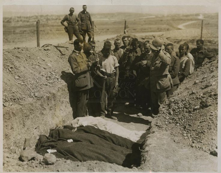 Photograph of three British Army chaplains (Church of England, Roman Catholic and Presbyterian) with burial party at graveside of four dead soldiers. No 2724. From a collection of official photographs of the Dardanelles Expedition, 1915-1916.