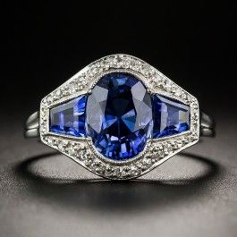 Original 1920s-30s Art Deco perfection. A seamless blast of radiant royal blue, created by a central faceted oval sapphire embraced on each side by a trapezoid sapphire, is bordered  all around with tiny diamond twinklers in this sleek and exceptional jewel. Hand-fabricated in platinum in France. 3.20 carat total sapphire weight. Currently ring size 5 1/2 (with sizing beads).