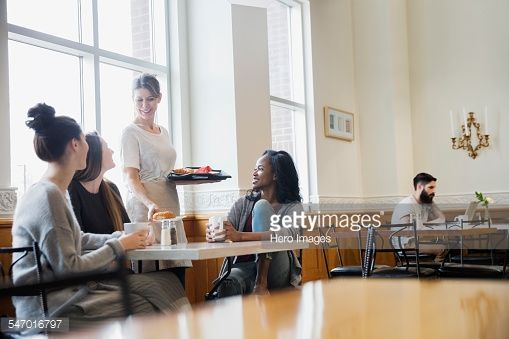 Stock Photo : Woman serving friends at cafe table