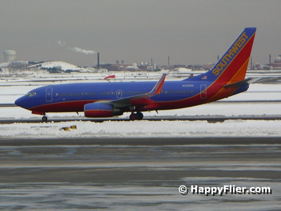 A Southwest Airlines jet taxiing at Boston Logan International Airport, with snow in the background.