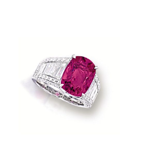 PINK SAPPHIRE AND DIAMOND RING. Centring on a cushion-shaped pink sapphire weighing 7.02 carats, to a stylised mount set with tapered baguette and brilliant-cut diamonds together weighing approximately 2.50 carats, mounted in 18 karat white gold