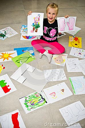 A preschool girl sitting on the floor presenting her pictures, drawings and paintings done at kindergarten.
