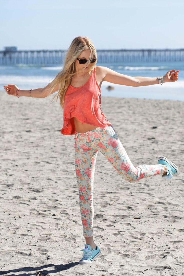 Shea Marie is wearing a coral top from Forever 21, floral pants from Zara, light blue shoes from Converse and sunglasses from RayBan