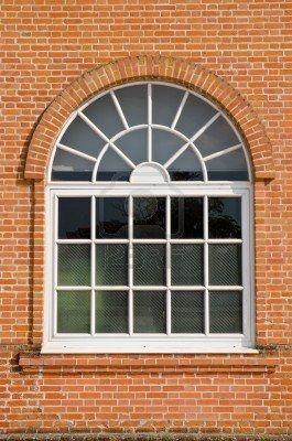 pintada de blanco madera de la ventana de arco en una pared de ladrillo rojo
