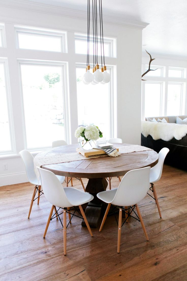 A rustic round wood table surrounded by white Eames dining chairs creates  an interesting mix in