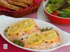 Salmone al forno con curcuma e limone, completato da insalata e pane integrale ai semi di lino, un secondo piatto appetitoso ed equilibrato.
