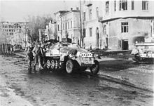 SS-Standartenführer Fritz Witt, the commander of a SS Panzer Grenadier Regiment and a recipient of the Knight's Cross with Oak Leaves, advances in the cover of an armoured personnel carrier along Sumskaya street (Сумская ул.) in Kharkov. The city was recaptured by the Waffen-SS on March 14, 1943.